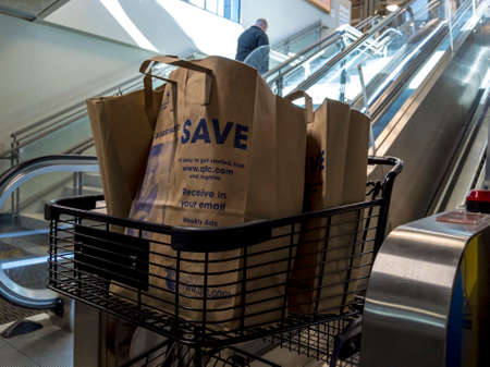 Seattle, WA / USA - circa May 2020: View of a shopping cart exiting the cart escalator inside a QFC grocery store, filled with bags of groceries.