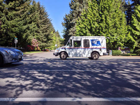 Seattle, WA / USA - circa April 2020: Street view of a USPS mail truck in a Seattle area neighborhood, delivering mail during the COVID-19 pandemic.