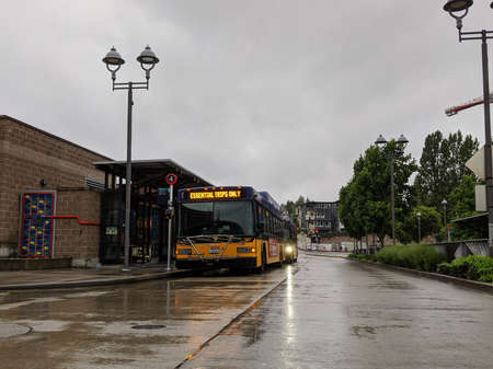 Kirkland, WA / USA - circa May 2020: Street view of a King County Metro bus stating 'Essential Trips Only' on its transit screen.