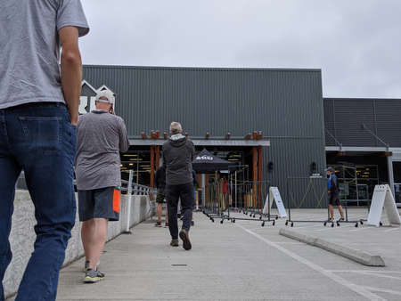 Bellevue, WA / USA - circa June 2020: People wearing masks lined up outside at REI Outdoor Store.