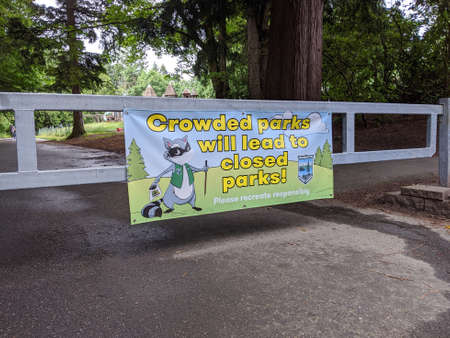 Kirkland, WA / USA - circa March 2020: Sign stating 'Crowded Parks Lead to Closed Parks' at St. Edwards Park. Editorial