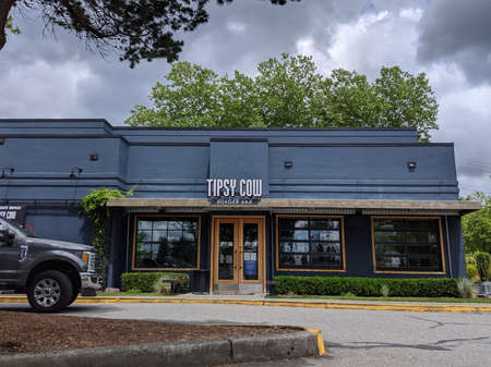 Woodinville, WA / USA - circa July 2020: Curbside view of a Tipsy Cow Burger Bar on a sunny day