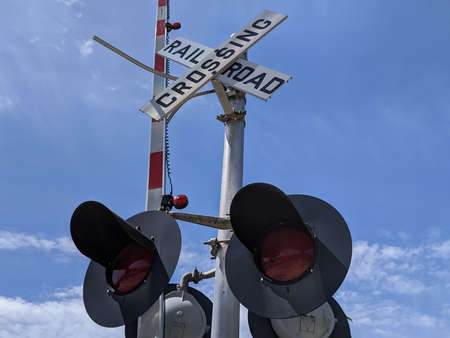 Low angle view of traffic lights at a railway crossroad in a quiet small town