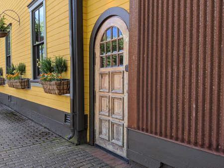Angled view of a rustic, wooden door in a historic downtown area, flower beds by the windows Standard-Bild