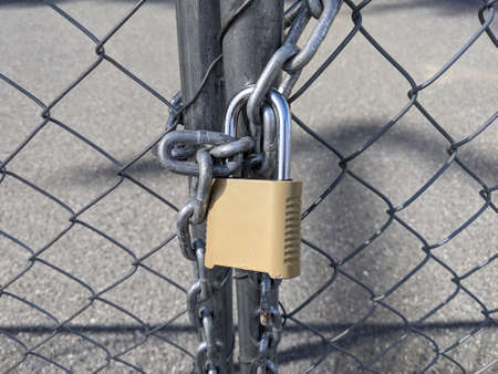 Close up of a yellow padlock and chain keeping a chainlink fence sealed Standard-Bild