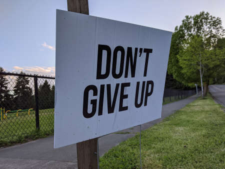 Angled view of a Don't Give Up motivational sign in a yard during the COVID-19 pandemic