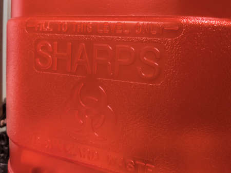 Close up view of a red sharps medical waste container inside a medical office Standard-Bild