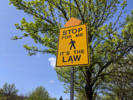 Low angle view of a Stop For Me It's The Law yellow street sign on a bright, sunny day Standard-Bild