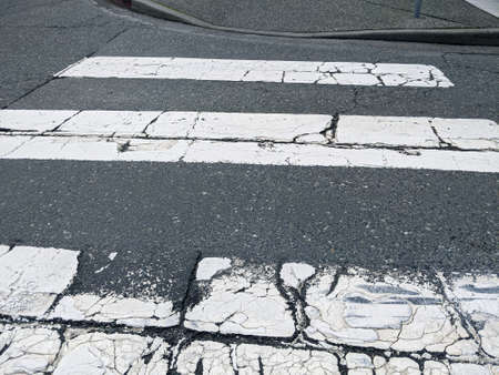 High angle view of a cracked, distressed striped crosswalk in a city downtown Standard-Bild
