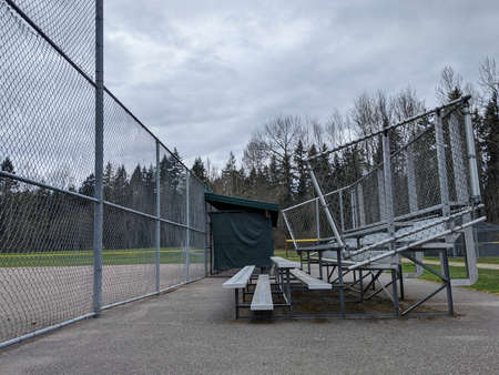 Side view of empty bleachers outside of a sports field on an overcast day at the park