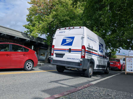 Kirkland, WA / USA - circa June 2020: Local USPS mail carrier van making its deliveries downtown.