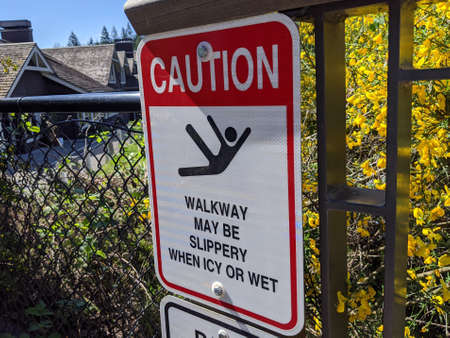 Angled view of a 'Caution: Walkway May Be Slippery' sign outside of Snoqualmie Falls Park