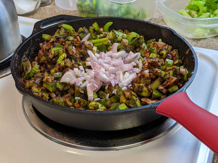 Side angle view of a cast iron skillet, filled with red and yellow onions, garlic, bell peppers, and celery Stock fotó