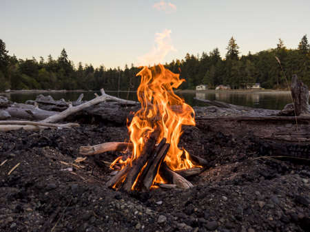 View of a bright, lakeside campfire at dusk, perfect for roasting smores