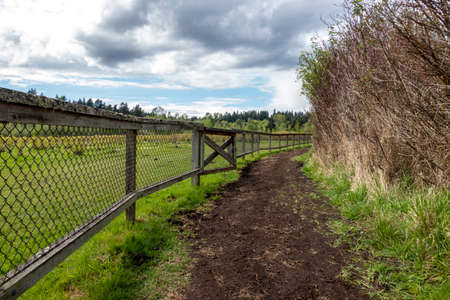 Beautiful view of a dirt path by a wooden fenced in farm on a cloud filled, sunny day