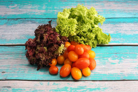 Tomato cherry with green and red leaf lettuce on top wooden table. Fresh ingredient for making healthy salad and sandwiches