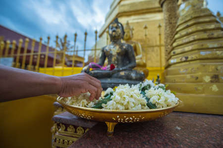 Putting garland in front of the Buddha image for respectation