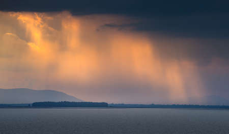 Sun beam penetrate the stormy cloud over the lake at golden sunset time