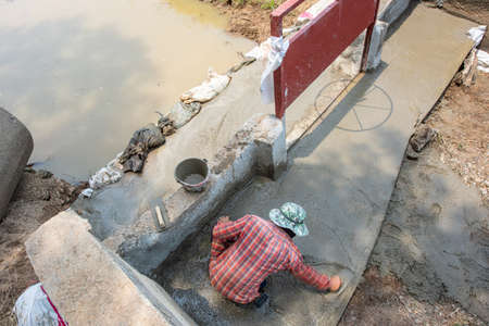 A labour man sweeping the ready-mix cement during water barrier construction