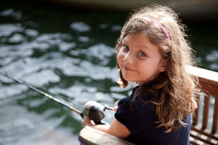 sunfish: A 5 year old girl fishing with a fishing pole, looking at the camera