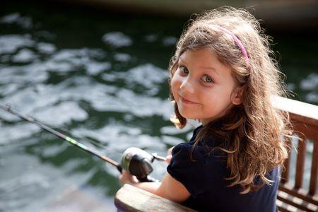 Een 5-jarige meisje met een hengel vissen, kijken naar de camera