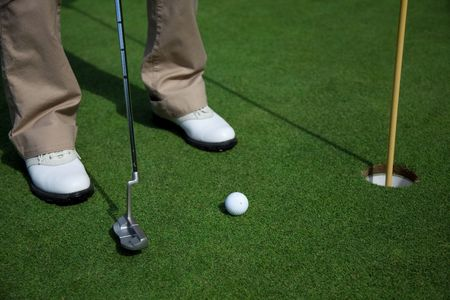 A woman putting into a golf hole with white shoes Stock Photo