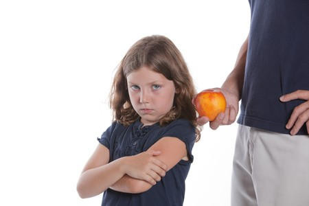 A cute little girl turns away as her father offers her a healthy snack apple Stock Photo - 8255593