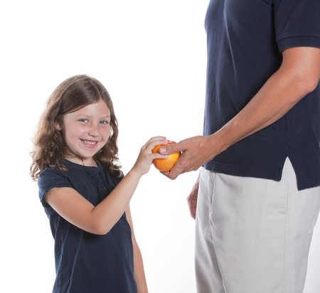 A cute little girl smiles as her dad gives her an apple for a snack Stock Photo - 8255570