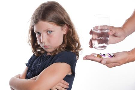 Een schattig klein meisje met een triest gezicht zich van haar ouders, niet bereid te nemen van de pil van de geneeskunde worden aangeboden  Stockfoto