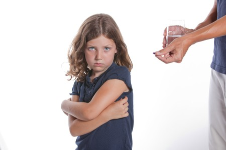 A adorable little girl with a sad face turns away from her parent, unwilling to take the medicine pill being offered Stock Photo