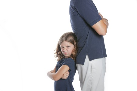 A cute sassy little girl shows she is upset during a conflict with her parent father