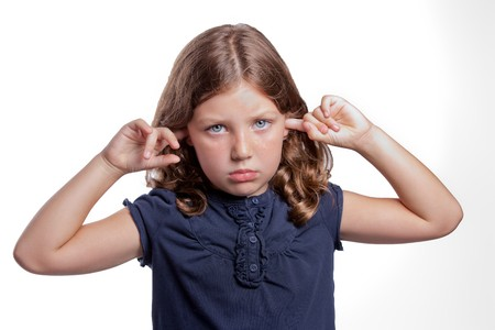 a cute little girl with big blue eyes covers her ears while making a sad face Stock Photo