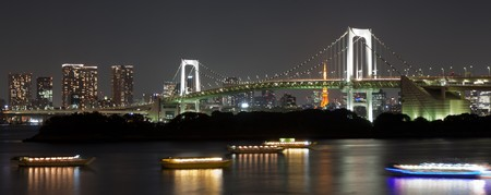 The Rainbow Bridge in Tokyo Japan at night with the skyline and Tokyo Tower int he background
