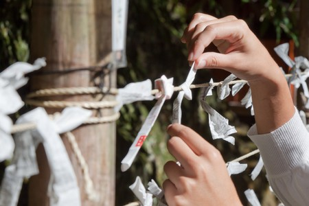 A woman ties her Omikuji furtune paper to a string in a temple in Kyoto Japan Stock Photo - 8255806