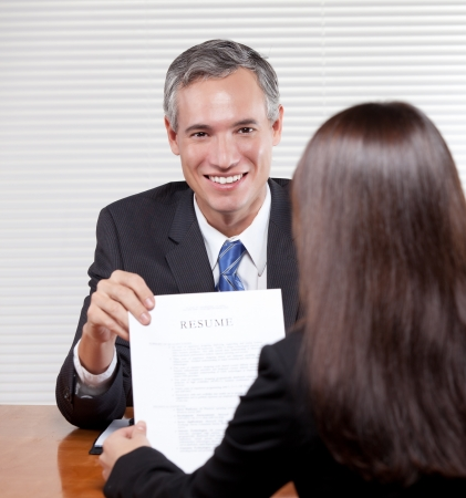 A handsome smiling man hands over a resume