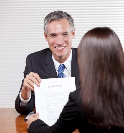 Een knappe lachende man in handen van een CV Stockfoto