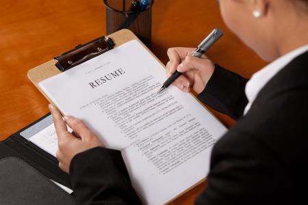 Een vrouw die met een pen in haar hand over een CV kijkt