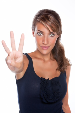 An attractive young woman smiles while holding up three fingers photo