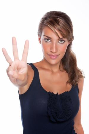 Een aantrekkelijke jonge vrouw glimlacht terwijl tot drie vingers Stockfoto