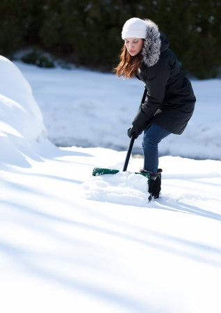 An attractive young woman looking down while shoveling her driveway