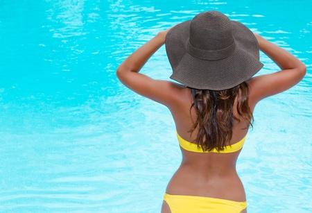 Woman in hat and bikini near pool