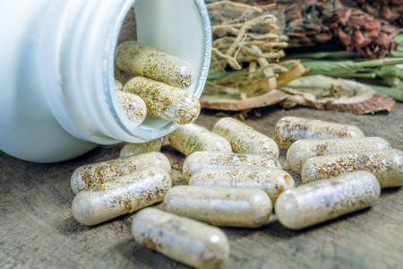 Alternative chinese herbal medicine on capsule at wooden table