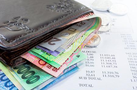 Oude lederen portefeuille en geld in diverse bankbiljetten en munten op de creditcard of een financieel overzicht Concept van het betalen van de schulden
