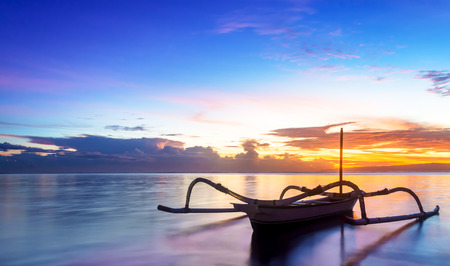 sanur: Jukung traditional bali fishing boat on sunrise near sanur   beach facing the ocean  The traditional style canoe is   fitted with two bamboo act as stabilisers  Concept of   journey, hope, new beginning, tranquility and serenity in seaside