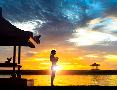 Silhouette of young woman practising yoga meditation in standing full lotus position near gazebo or   pagoda at beach in Bali during sunrise or sunset with her dog. Sanur beach has many gazebo facing the ocean.
