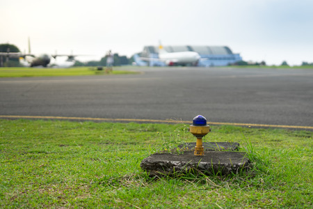 Safety Edge Blue Light Beside Airport Taxiway with Blur Airplane on Background