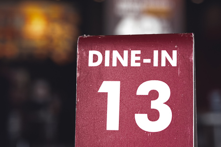 Restaurant dine in table top sign holders. Queueing serving unlucky number 13 with dark moody bokeh background
