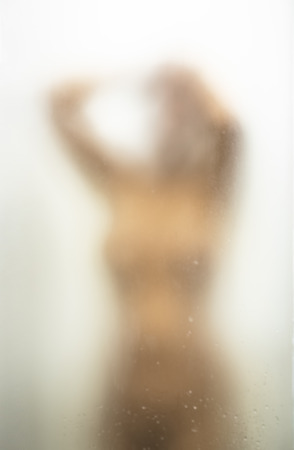 Young Woman Taking Shower or Junub Bath After washing Her Hair. Concept of Health, Hygiene and self Care. Shoot Through Blurry Iced Bathroom Glass.