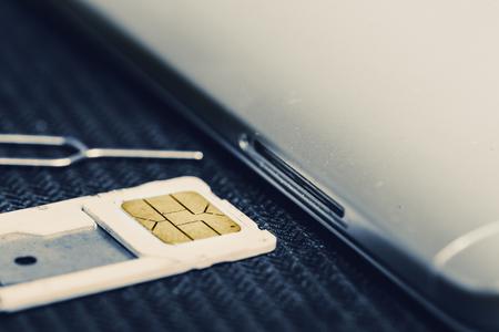 Öffnen Sie das Fach der Micro-SIM-Karte neben dem Smartphone. Konzept des Änderns oder Wechselns zu einer neuen Sim-Karte Standard-Bild