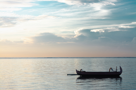 Traditional Bali Fishing Boat Without Passenger Floating On A Very Calm and Peaceful Ocean After Sunrise in Cloudy Morning Sky. Cloud Formation is Altostratus. Concept of Waiting, Peaceful and Joy